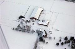 Winter aerial view of house, barn, and arena